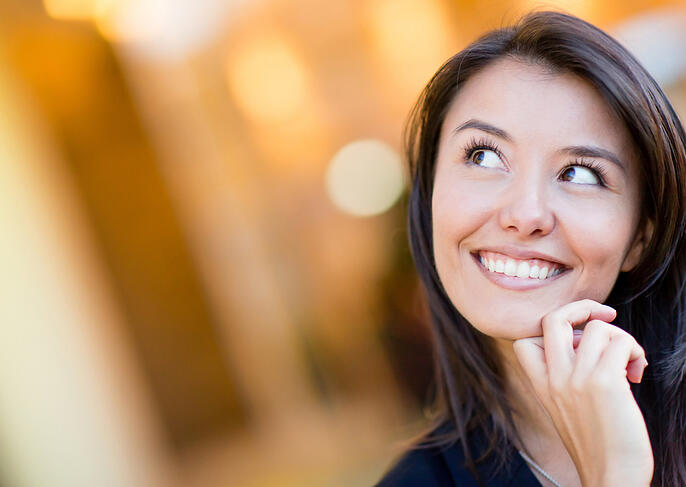 Portrait of a thoughtful woman looking up and smiling