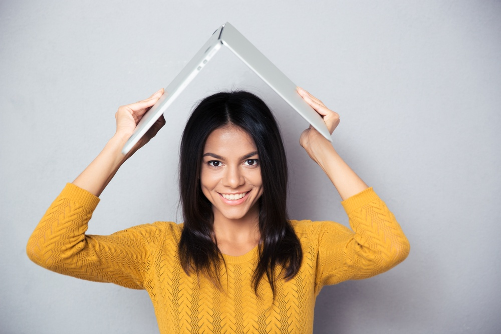 Happy woman in sweater holding laptop above her head like a roof over gray background. Looking at camera.jpeg